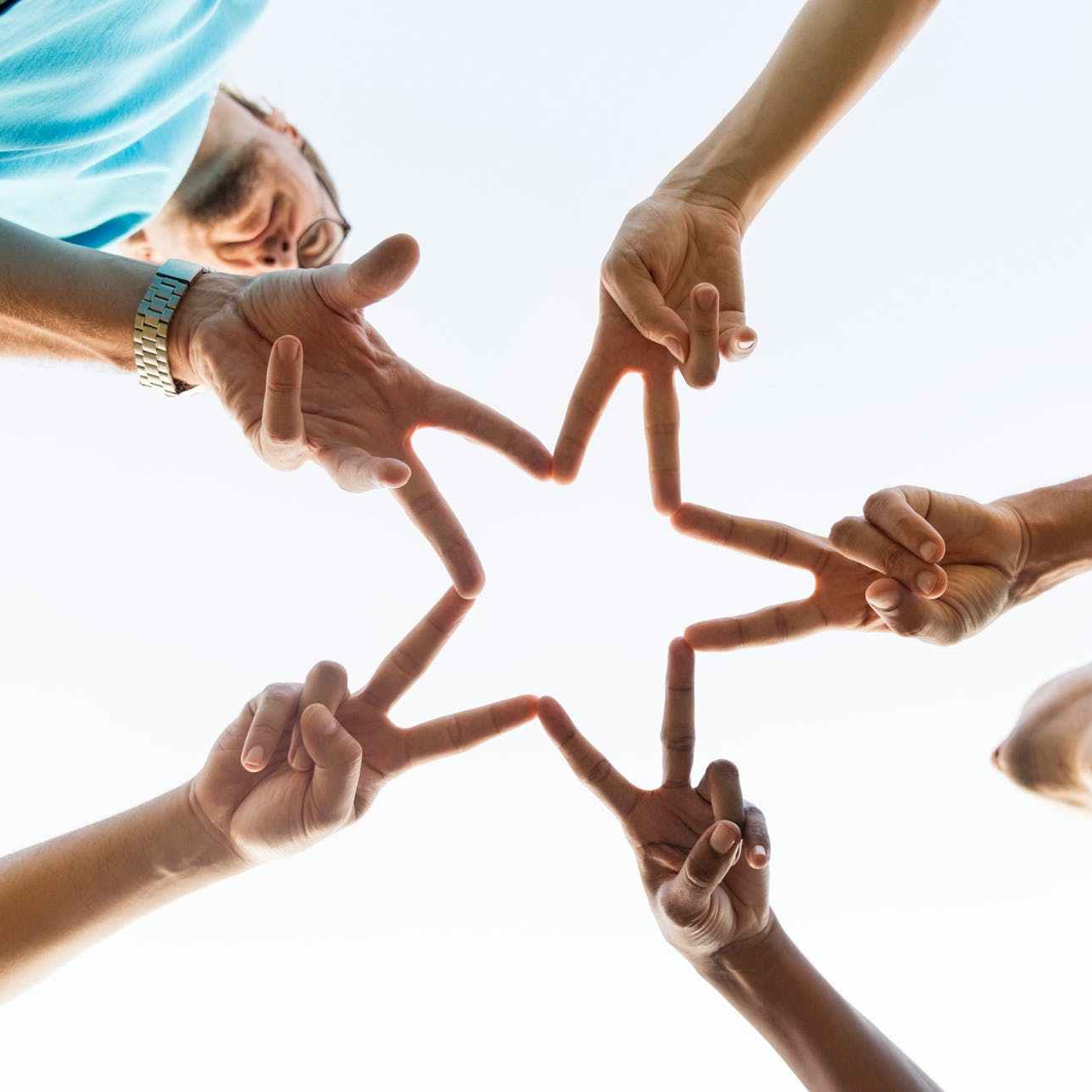 group of people doing star handsign